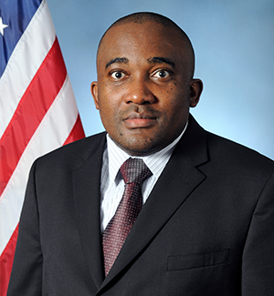 Charles A. Kamhoua  by the American flag